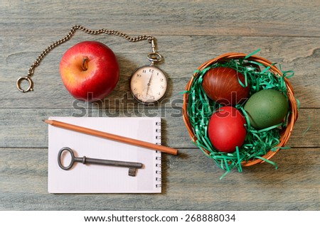 Easter eggs in a basket, apple and pocket watch on the table - stock photo