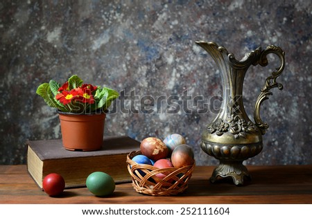 Easter eggs in a basket of wicker and metal carafe - stock photo