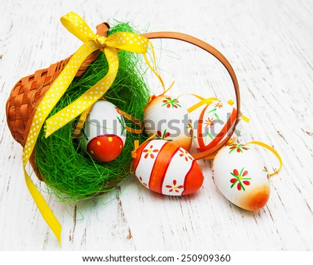 Easter eggs in a basket on a old wooden background - stock photo