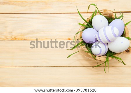 Easter eggs in a basket on rustic wooden background - stock photo