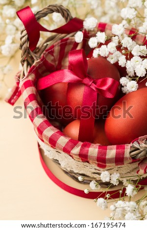 Easter eggs in a basket with red checkered napkin (close-up) - stock photo