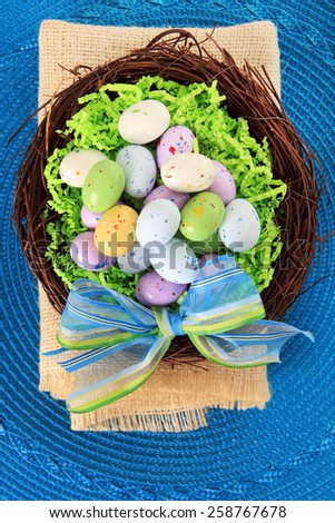 Easter eggs in a nest on a blue background.   - stock photo