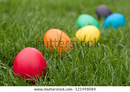 Easter eggs in a row on the meadow - stock photo