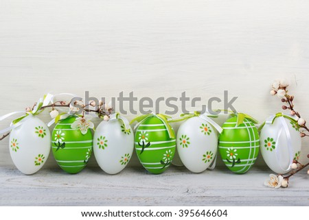 Easter eggs in a row with blooming cherry branches on wooden background