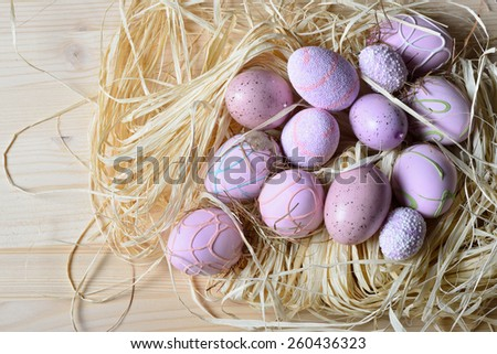 Easter eggs in a straw nest on a wooden table