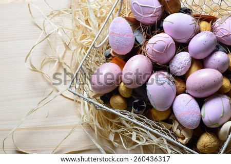 Easter eggs in a white wire basket on a wooden table
