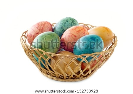 Easter eggs in a wicker basket on a white background