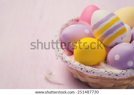 Easter eggs in a wicker basket with space for text - stock photo