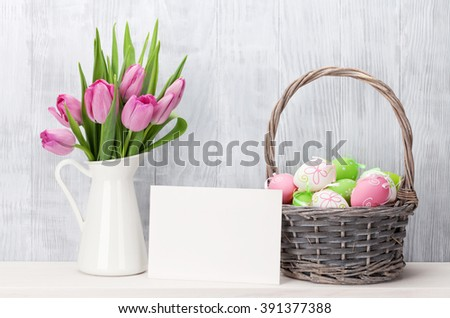 Easter eggs in baasket, greeting card and pink tulips bouquet on shelf in front of wooden wall. View with copy space - stock photo