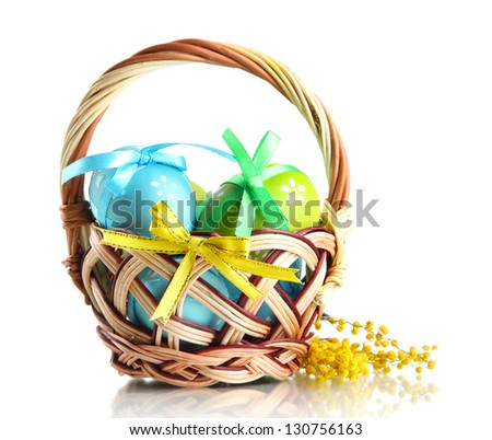 Easter eggs in basket and mimosa flowers, isolated on white