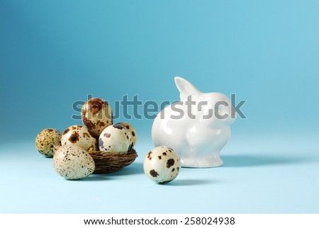 Easter eggs in basket and white porcelain Easter Bunny over blue background - stock photo