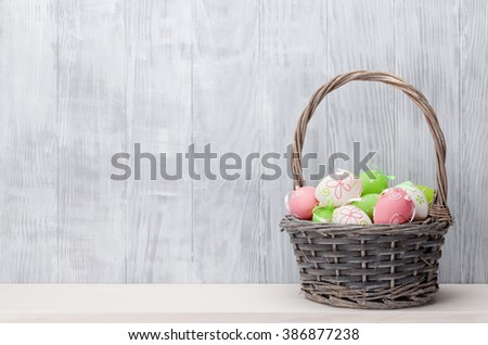 Easter eggs in basket on shelf in front of wooden wall. View with copy space - stock photo