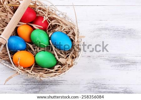 Easter eggs in basket on vintage wooden planks background - stock photo