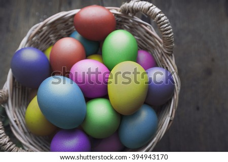 Easter eggs in basket on wooden board - stock photo
