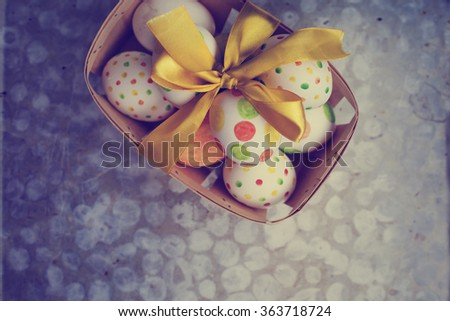 easter eggs in basket with bow on rusty background   - stock photo