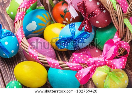easter eggs in brown basket. Focus on the pink bow and handle basket - stock photo