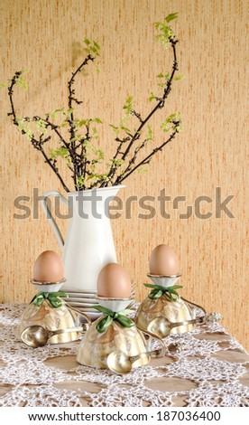 Easter eggs in eggcups with gold spoons. Next currant branches with leaves and flowers