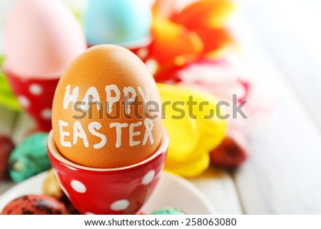 Easter eggs in holders and tulip flowers on wooden background - stock photo
