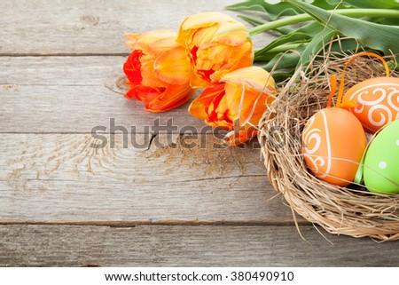 Easter eggs in nest and tulip flowers on wooden table. View with copy space - stock photo