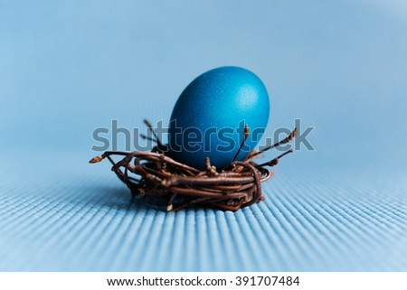 Easter eggs in nest on blue background - stock photo