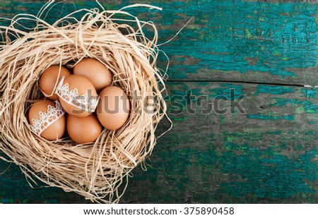 Easter eggs in nest on rustic wooden planks. Holidays background  - stock photo
