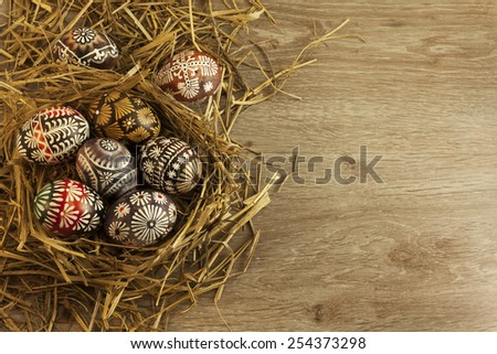Easter eggs in nest on wooden background - stock photo