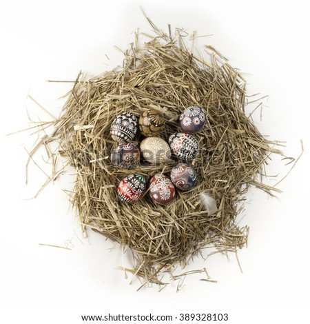 Easter eggs in straw nest isolated on white background