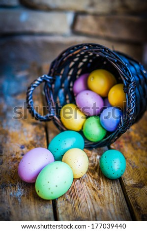 Easter eggs in the basket on rustic wooden background - stock photo