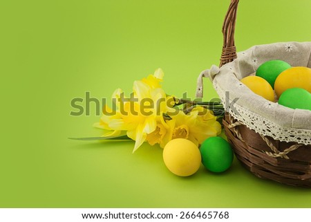Easter eggs in the basket with bouquet of yellow lent lily daffodil or narcissus on green background. - stock photo