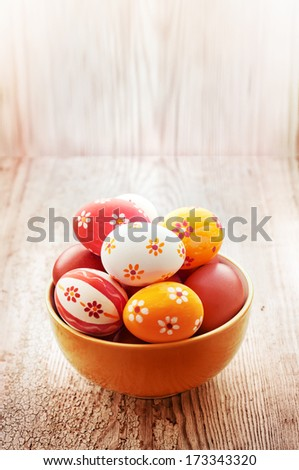 Easter eggs in the bowl on texture bright wooden background - stock photo