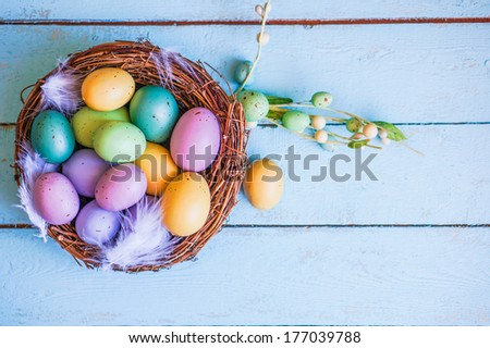Easter eggs in the nest on blue wooden background - stock photo