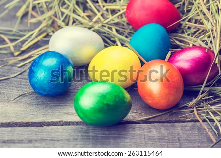 Easter eggs in the nest on rustic wooden background. Blue toned - stock photo