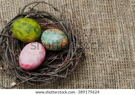 Easter eggs in the nest on wooden background.Rustic style.Top view. Free space for text.
