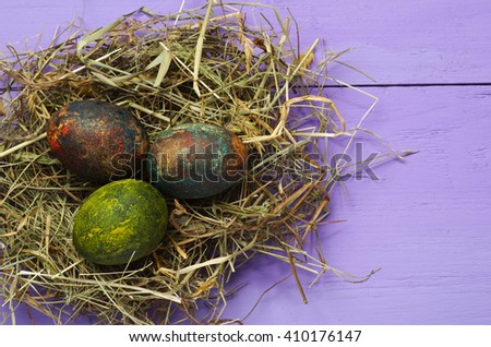 Easter eggs in the nest on wooden background.Rustic style. Top view. Free space for text.