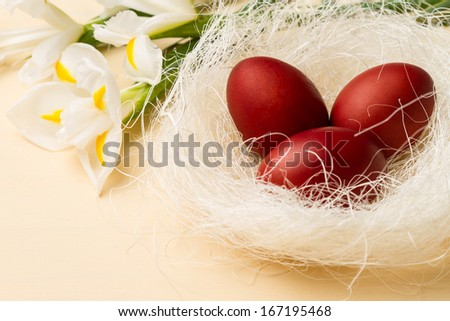 Easter eggs in the whitish nest and white flowers on the beige table - stock photo