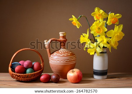 Easter eggs in wicker baskets and flowers on the table - stock photo