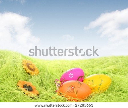 Easter Eggs laying on grass field with blue sky background