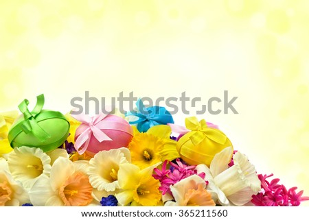 Easter eggs, narcissus and hyacinth on abstract background with space for text. - stock photo
