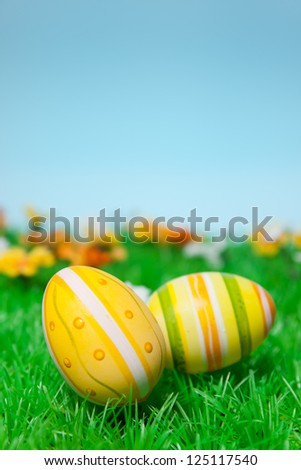 Easter eggs on a well-kept lawn in front of blue heaven