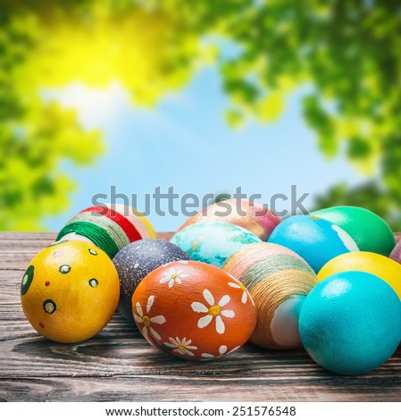 Easter eggs on a wooden table on a background of nature - stock photo