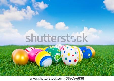 Easter Eggs on Fresh Green Grass over blue sky - stock photo