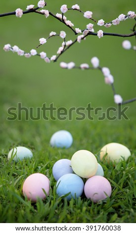 Easter eggs on green grass under blooming cherry branches. - stock photo