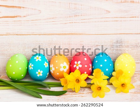 Easter eggs on meadow with daffodil flower - stock photo