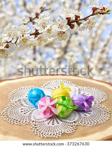 Easter eggs on wood surface (oak) on background of blooming apricot tree. - stock photo