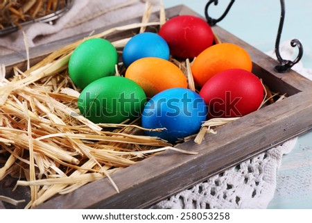 Easter eggs  on wooden tray, on colorful background - stock photo