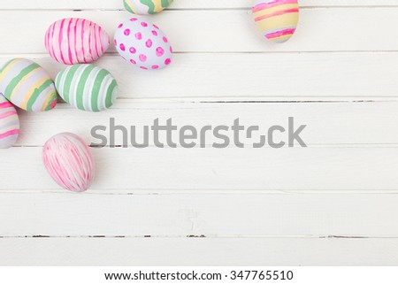 Easter eggs painted in pastel colors on a white wood background - stock photo
