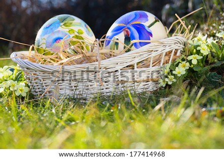 Easter eggs painted with flowers in a basket . Spring celebration - stock photo