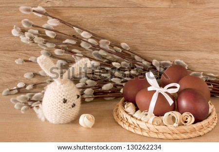 Easter eggs, rabbit and  catkins on a wooden background - stock photo