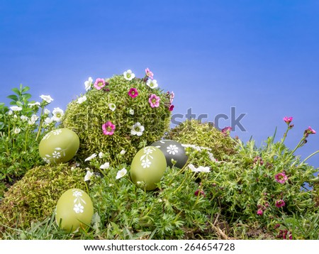 Easter eggs scattered in the grass and giant moss-grown egg with fresh spring flowers over blue sky - stock photo