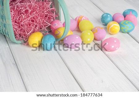 Easter Eggs spilling from a Basket in a row at top of background of white boards with room or space below for copy, text.  Horizontal - stock photo